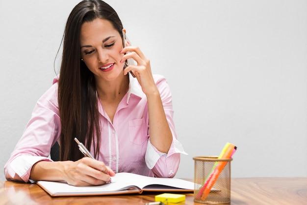 Mulher de visão frontal escrevendo estatísticas