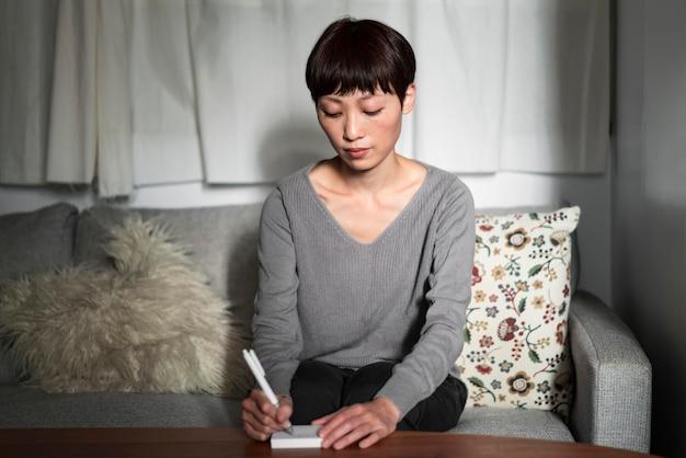 Mulher de visão frontal escrevendo mensagem