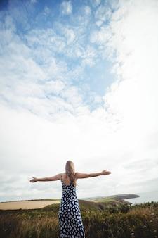 Mulher de visão traseira em pé com os braços estendidos