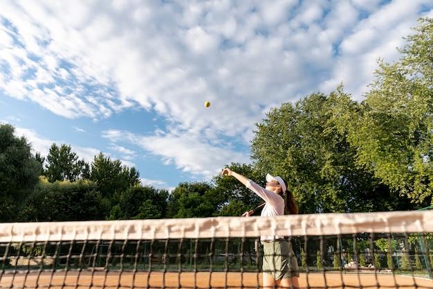Mulher de vista baixa servindo durante partida de tênis
