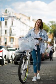 Mulher de vista frontal andando ao lado de sua bicicleta