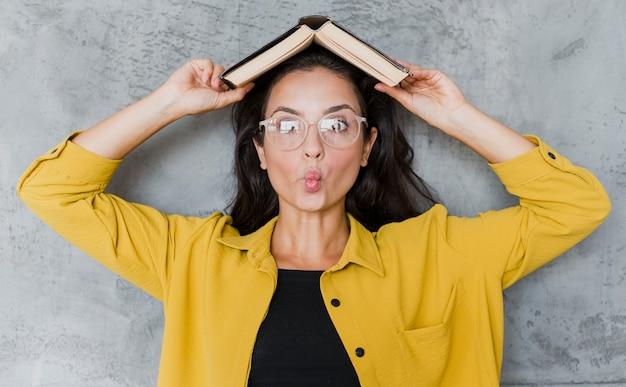 Mulher de vista frontal com livro e óculos