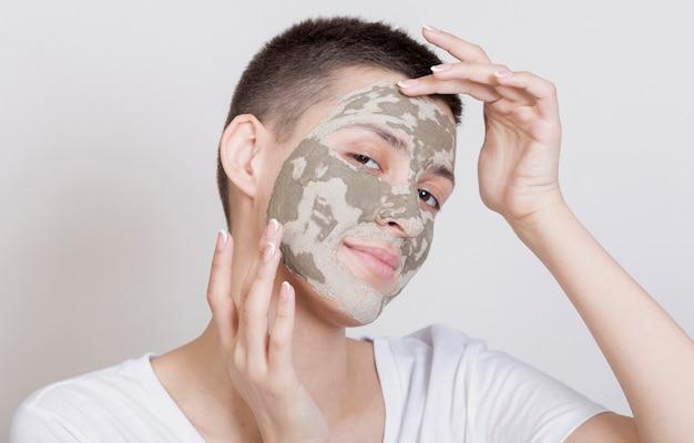 Mulher de vista frontal com máscara facial, olhando para a câmera