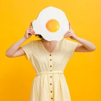 Mulher de vista frontal com ovo frito gigante