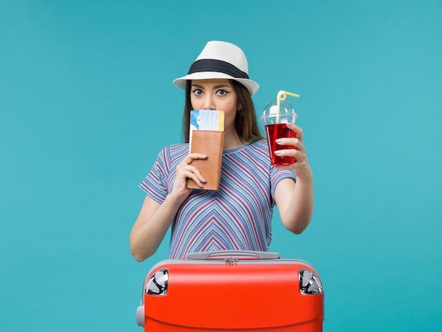 Mulher de vista frontal em férias segurando suco com ingressos na mesa azul viagem viagem avião marítimo feminino verão