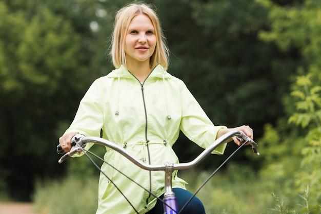 Mulher de vista frontal na bicicleta a desviar o olhar