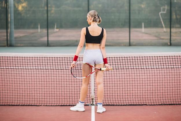 Mulher de vista frontal no campo de tênis médio