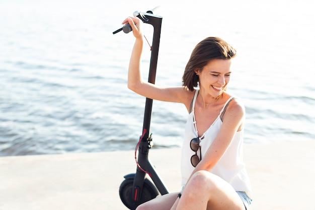 Mulher de vista frontal sorrindo e posando em uma scooter