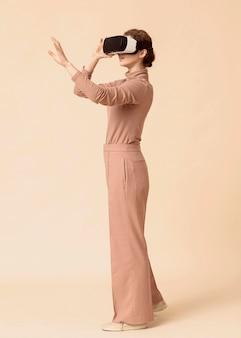 Mulher de vista lateral jogando em um fone de ouvido de realidade virtual