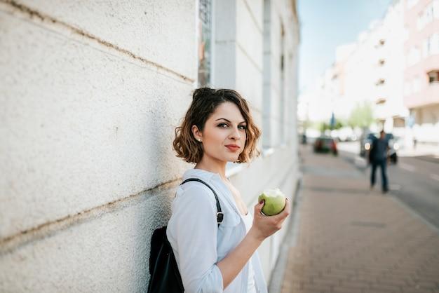 Mulher de vista lindo que come a maçã na rua.
