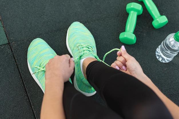 Mulher de vista superior, amarrando o tênis verde