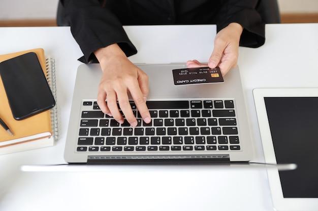 Mulher de vista superior com as mãos sentadas, segurando um cartão de crédito e usando o laptop na mesa