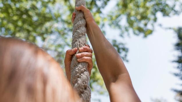 Mulher de vista traseira escalando uma corda