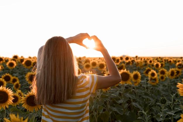 Mulher de vista traseira posando ao pôr do sol