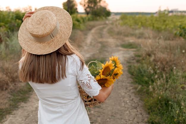 Mulher de vista traseira posando em uma estrada rural