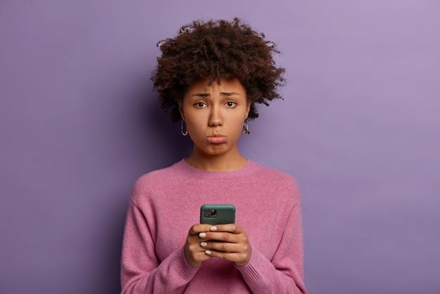 Mulher decepcionada e infeliz com cabelo afro, franze o lábio inferior, segura smartphone, triste por perder chance de uma boa liquidação, chateada por não receber ligação do namorado, posa dentro de casa, vestida casualmente