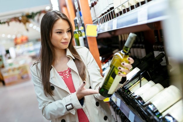 Mulher decidindo que vinho comprar e fazendo compras no supermercado