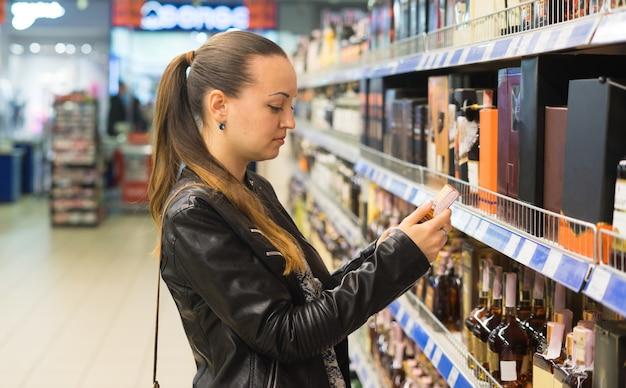 Mulher decidindo que vinho ou álcool comprar. compras no conceito de supermercado