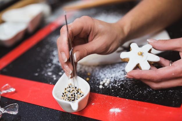 Mulher decora biscoitos de gengibre de natal com glacê de açúcar esmalte floco de neve. presente de natal, pão caseiro