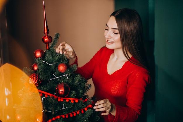 Mulher decorando a árvore de natal no natal