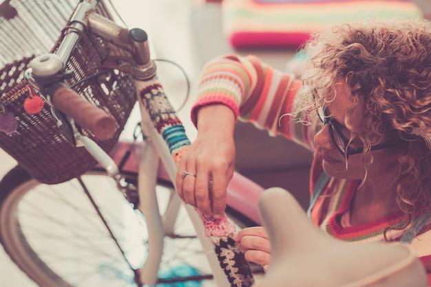 Mulher decorando a haste da bicicleta com tecido de lã. mulher com cabelo encaracolado e óculos, decorando ou modificando sua bicicleta com tecido de malha de lã na haste. mulher criativa decorando sua bicicleta.