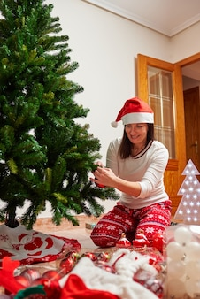 Mulher decorando árvore de natal artificial