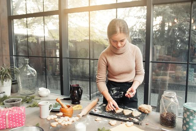 Mulher decorando biscoitos antes de assar