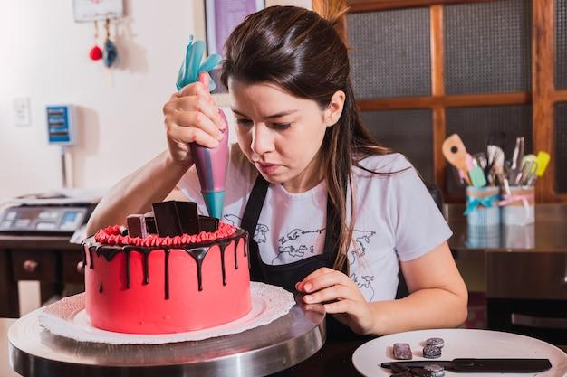 Mulher decorando bolo de chocolate na cozinha.