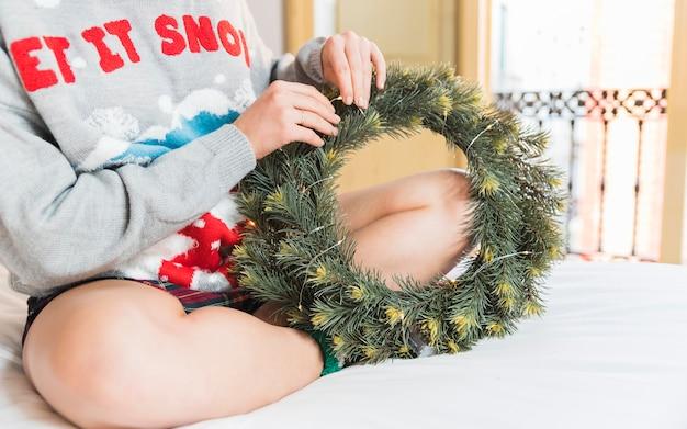 Mulher, decorando, verde, grinalda natal, cama