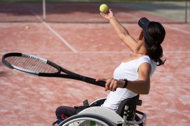 Mulher deficiente com tiro médio segurando bola