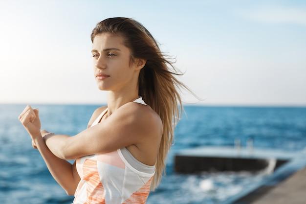 Mulher definir meta, manter o corpo em forma, esticar os braços, fazer exercícios de aquecimento para correr parecendo determinada