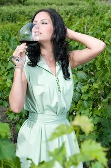 Mulher degustando vinho de sua adega em um vinhedo