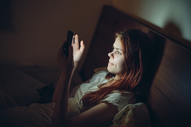 Mulher deita-se da cama à noite com um telefone no quarto virtual de descanso de mãos.