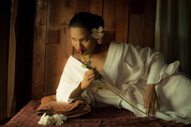 Mulher deitada cheira uma flor