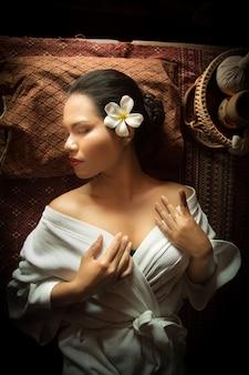 Mulher deitada com as mãos no peito