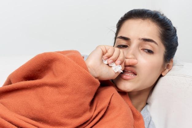 Mulher deitada com os olhos fechados, coberta com um cobertor de tratamento frio