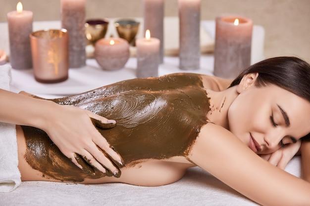 Mulher deitada com os olhos fechados e recebendo massagem de chocolate no salão de beleza