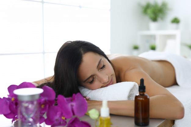 Mulher deitada com os olhos fechados na mesa de massagem