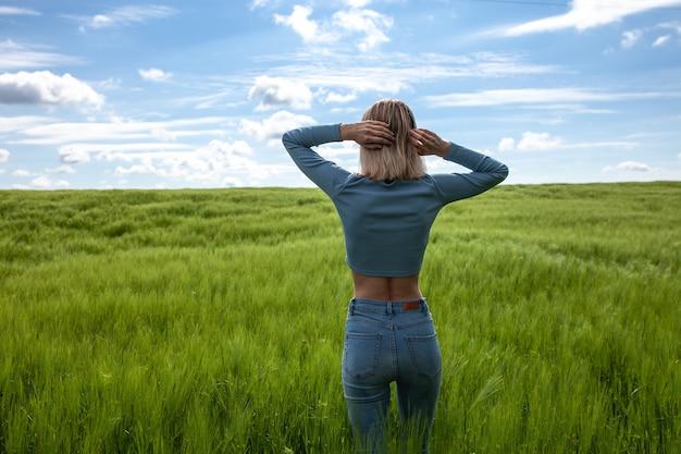 Mulher deitada de costas com os braços estendidos jovem magro no meio de um campo de trigo céu azul felicidade natureza férias de verão e conceito de pessoas jovem dançando no campo de costas