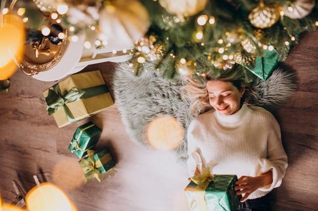Mulher deitada debaixo da árvore de natal com presentes