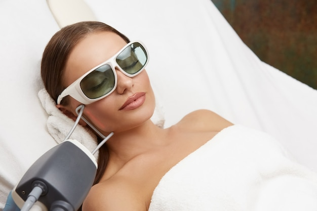 Mulher deitada em um salão de beleza e recebendo depilação a laser no rosto com óculos de proteção, uma linda mulher fazendo terapia a laser e depilação na bochecha