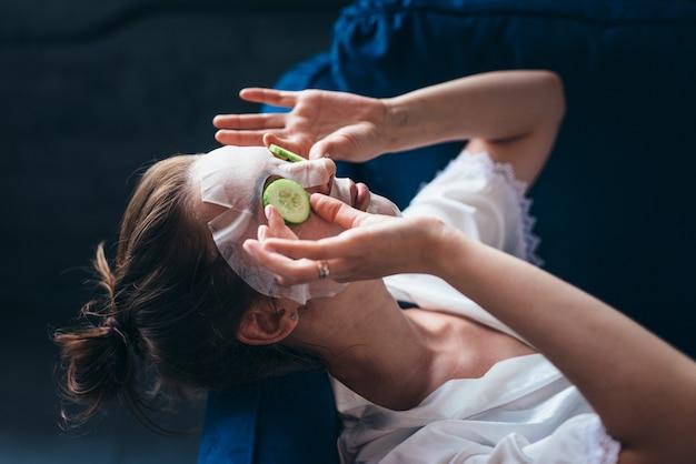 Mulher deitada em um sofá com uma máscara de lençol sobre o rosto e fatias de pepino