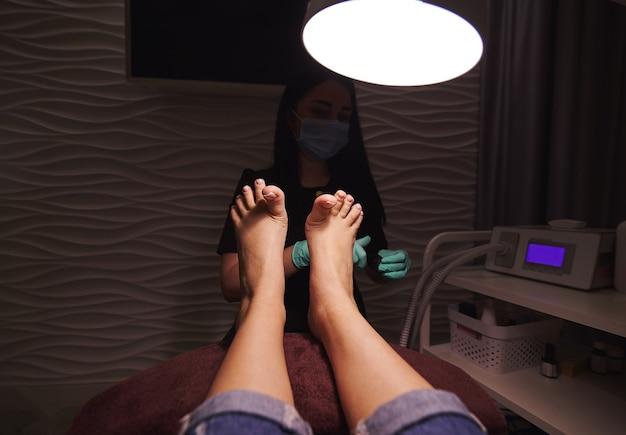 Mulher deitada em uma cadeira e desfrutando de pedicure profissional no salão de beleza.