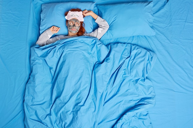 Mulher deitada em uma cama confortável sob o cobertor aplica máscara facial usa máscara de dormir e o pijama se sente solitário