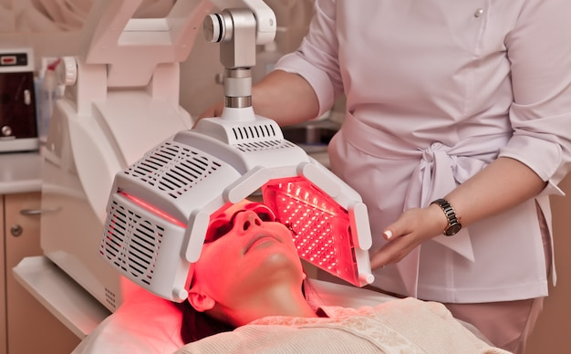 Mulher deitada em uma mesa com óculos de proteção nos olhos tem um tratamento de pele sob o dispositivo de beleza. salão de beleza spa.