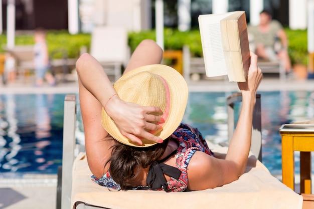Mulher deitada em uma rede enquanto lê um livro