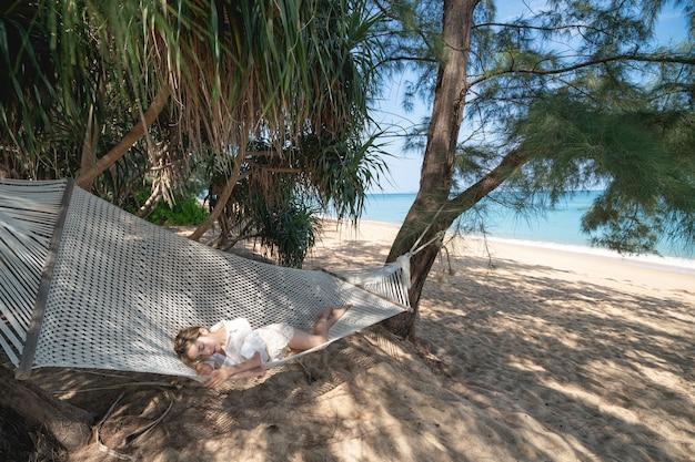 Mulher deitada em uma rede sob a sombra de uma árvore na praia.