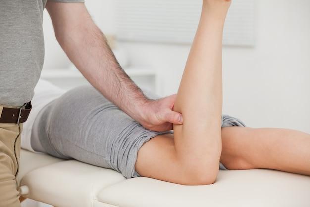 Mulher deitada enquanto um fisioterapeuta curvava a perna