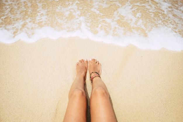 Mulher deitada na areia amarela do caribe perto da água transparente. conceito de férias e viagens relaxadas - nudismo e pernas nuas aproveitando o banho de sol e se bronzeando