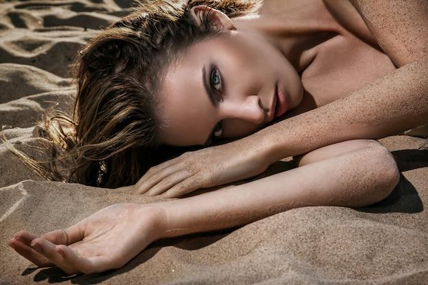 Mulher deitada na areia